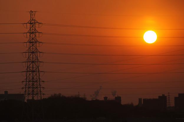 高圧電線帯を降りていく落陽